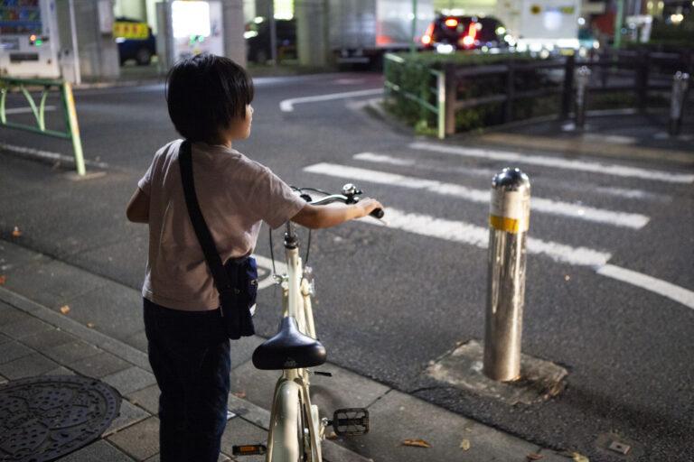 暗い夜道に1人で自転車を押し家に帰る子供