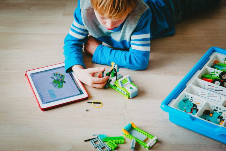 little boy building robot from plastic blocks and programming it with touch pad