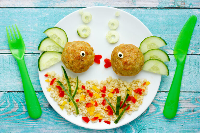 Food art idea healthy lunch for kids chicken meatballs with bulgur porridge and fresh vegetables shaped cute fishes