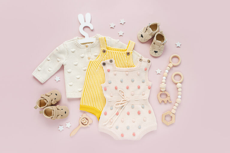 Set of baby clothes and accessories on pink background.  Various romper, bodysuit  baby shoes  and toys. Fashion newborn. Flat lay, top view