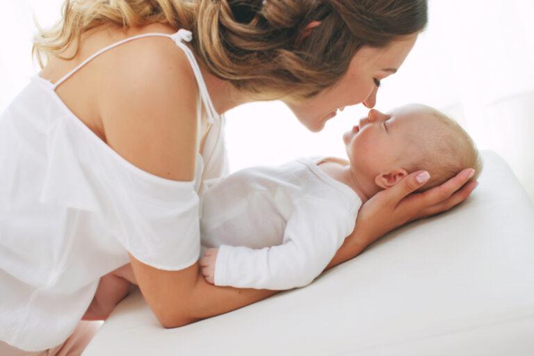 赤ちゃんの頭を優しく両手で抱き、鼻でキスする赤ちゃんとママ