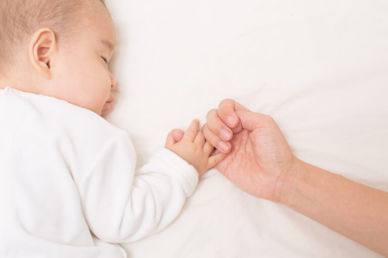 ママの小指を握りながら安心し、一緒に眠る赤ちゃん