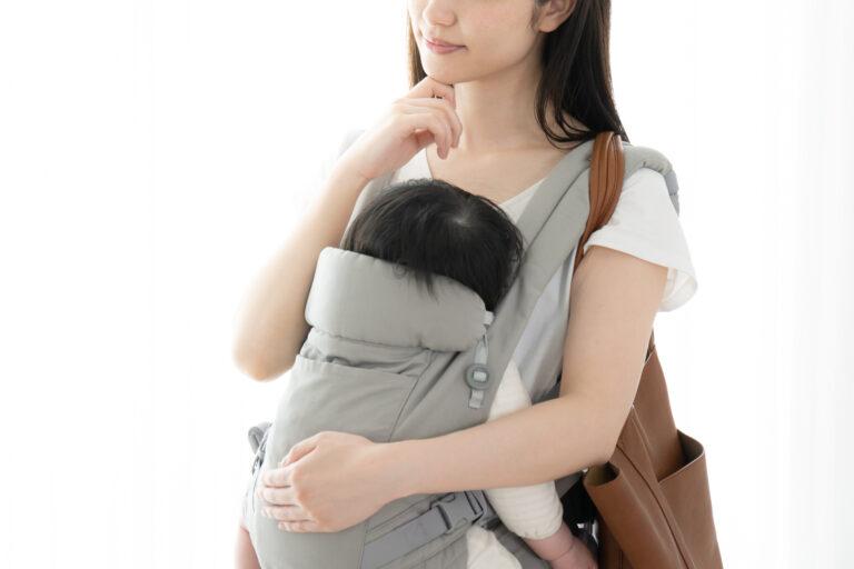 抱っこひも赤ちゃんを抱え、肩からバッグを提げて何かを考える母親