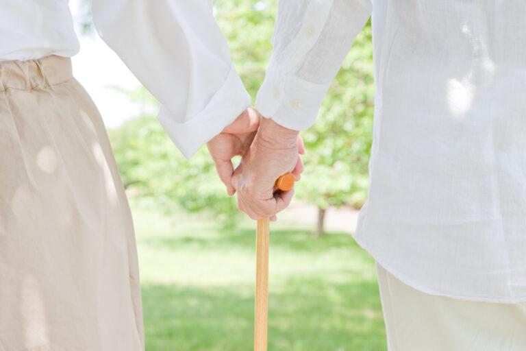 杖をつく夫と手を繋ぐ妻の老夫婦