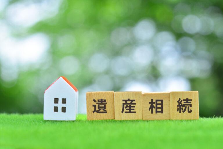 緑の上に並ぶ小さい家の模型と遺産相続という文字のブロック