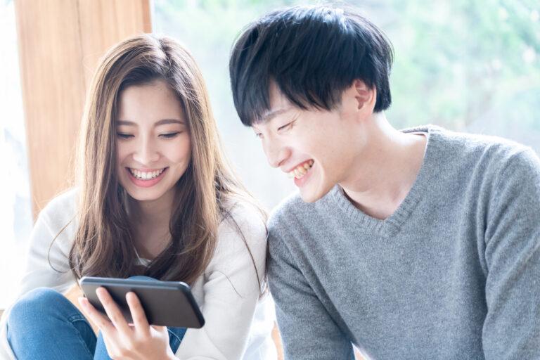 仲睦まじく笑顔で同じ画面を見る若い夫婦