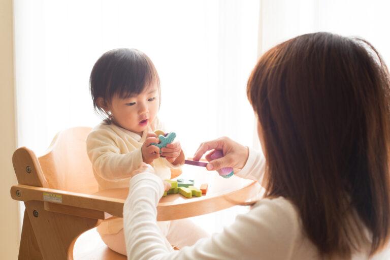 アルファベットのおもちゃを渡すママと興味津々にそのおもちゃを見つめる赤ちゃん