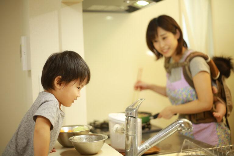 赤ちゃんをおんぶしながら料理をし、上の子どもに話しかけるママ