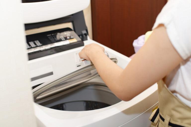 洗濯機を回すエプロン姿の女性