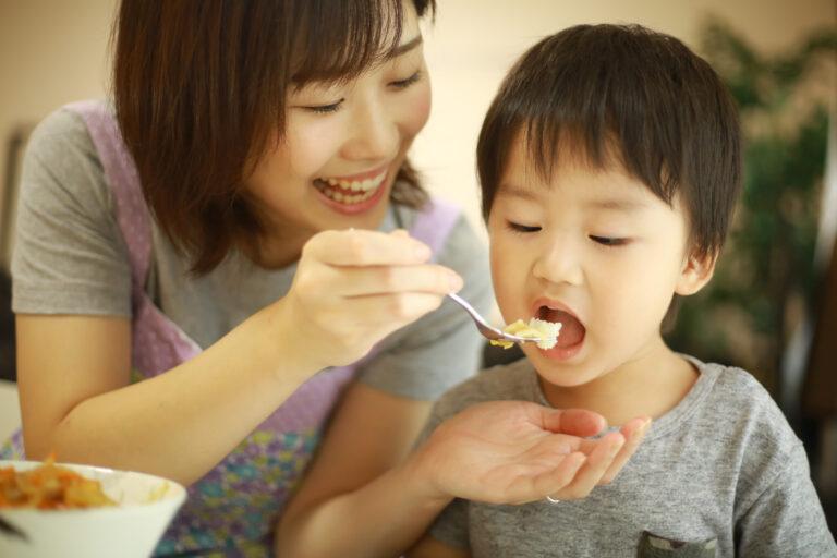 子どもに笑顔でご飯を食べさせるママ