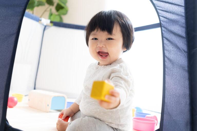 おもちゃを笑顔でママに手渡す赤ちゃん