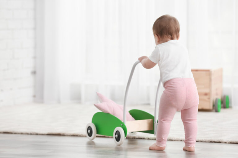 Cute baby with toy walker at home