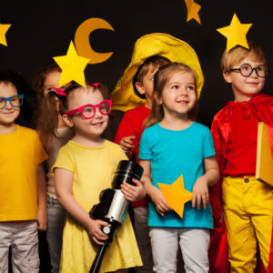 Six little friends, boys and girls in sky watchers costumes watching handmade stars and moon against black background